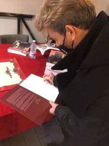 Centra firma una copia del suo libro